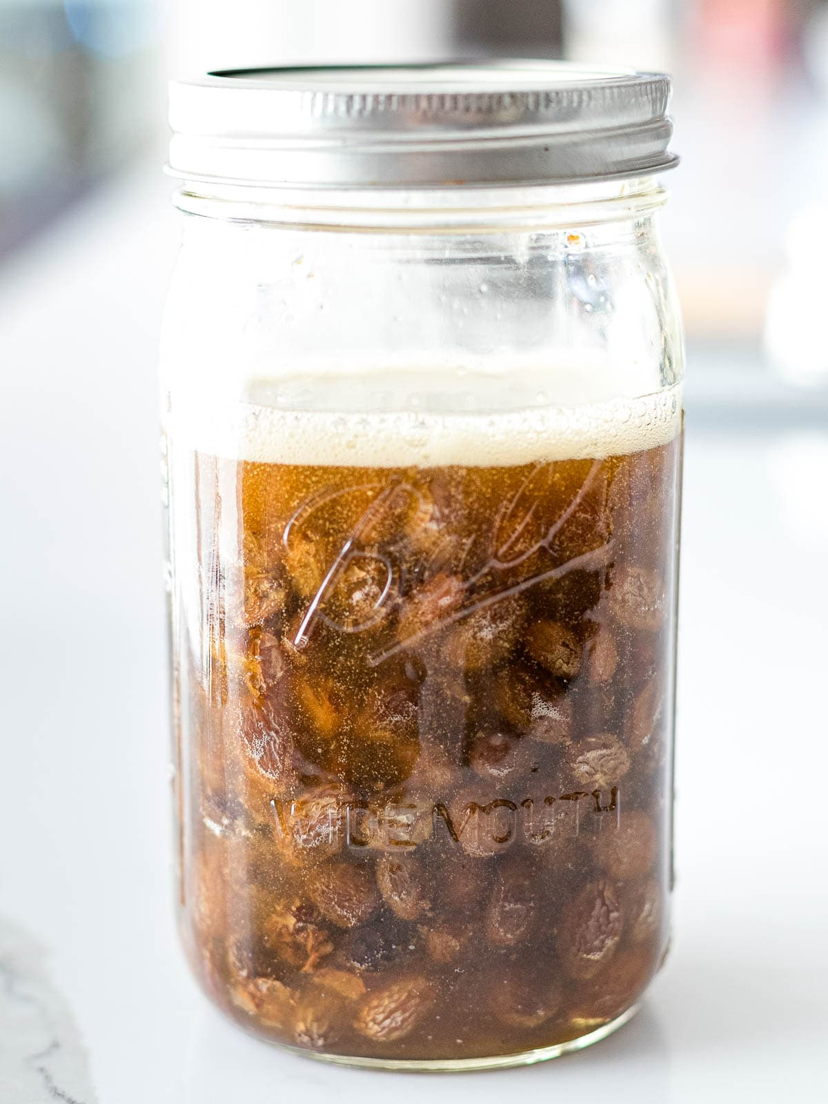 fruit yeast water in a mason jar with raisins and a foam layer on top