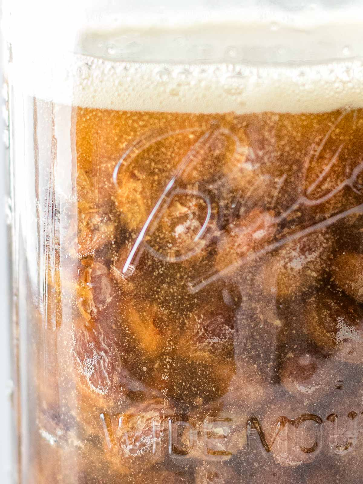 close up of raisin yeast water with bubbles and a foam layer