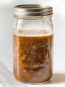 raisins fermenting in water with a foam layer on top inside a glass mason jar with a lid