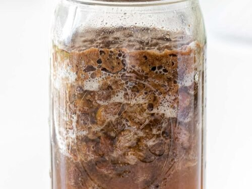fermented raisin yeast water showing bubbles and floating raisins in a glass mason jar with a lid