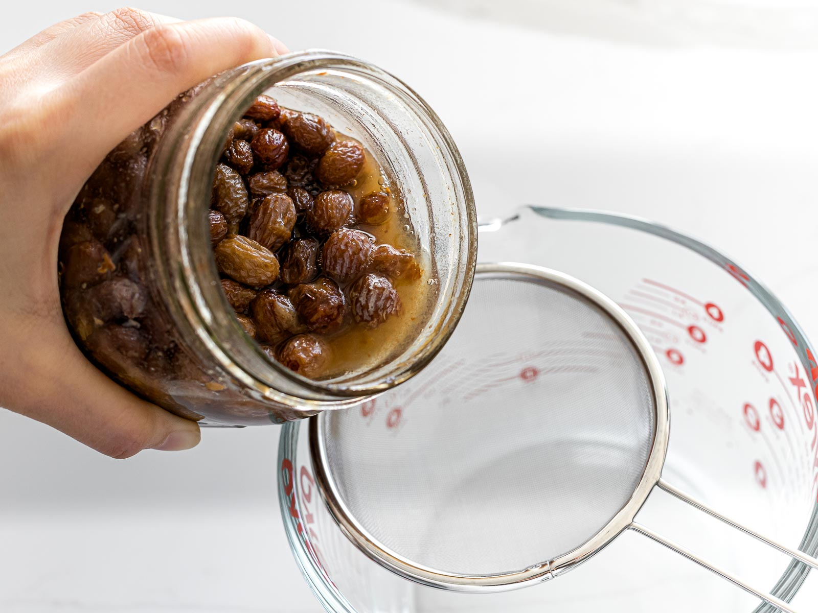 raisin yeast water being poured into a strainer