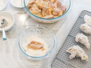 raw chicken wings being battered in flour and laying on a cooking rack