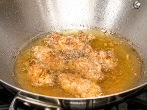 battered chicken wings double frying in oil in a metal wok