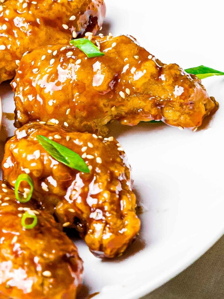 korean fried chicken with a soy garlic sauce with sesame seeds and scallions on a white plate