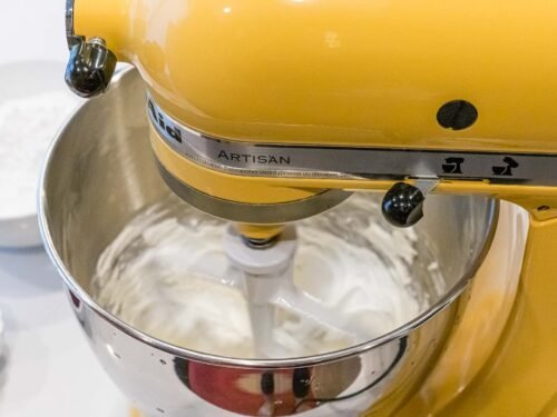 yellow stand mixer creaming butter and cream cheese together