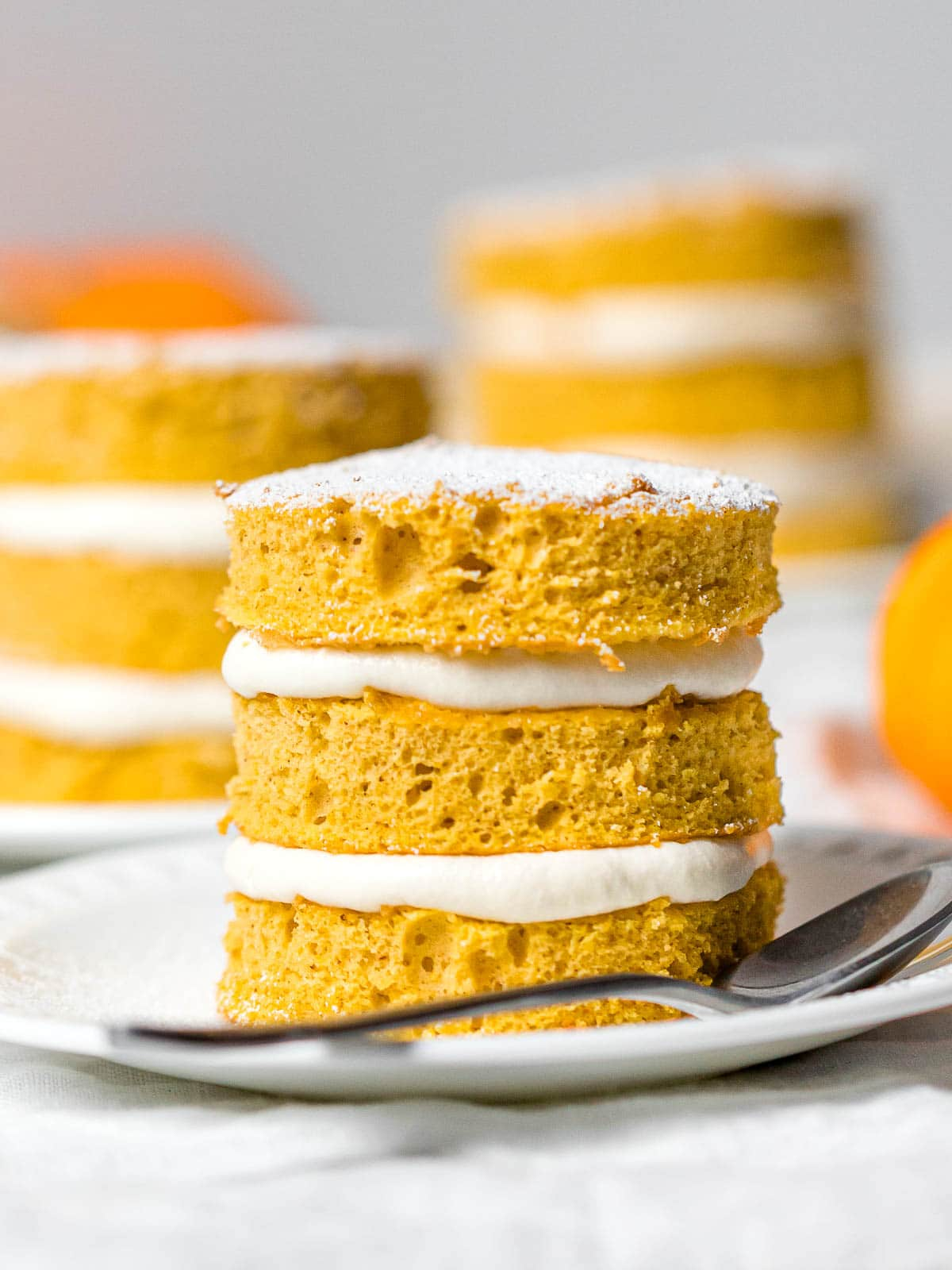 close up of a mini pumpkin layer cake with cream cheese frosting on a white plate next to a metal spoon