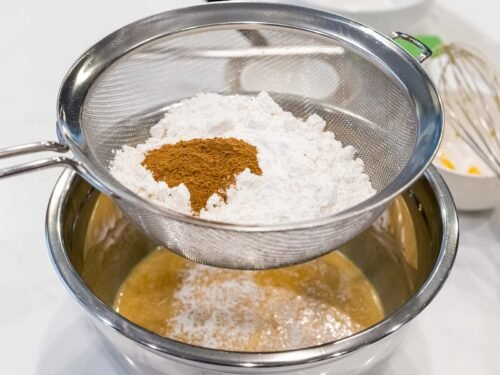 flour and pumpkin spice being sifted into a metal bowl with cake batter