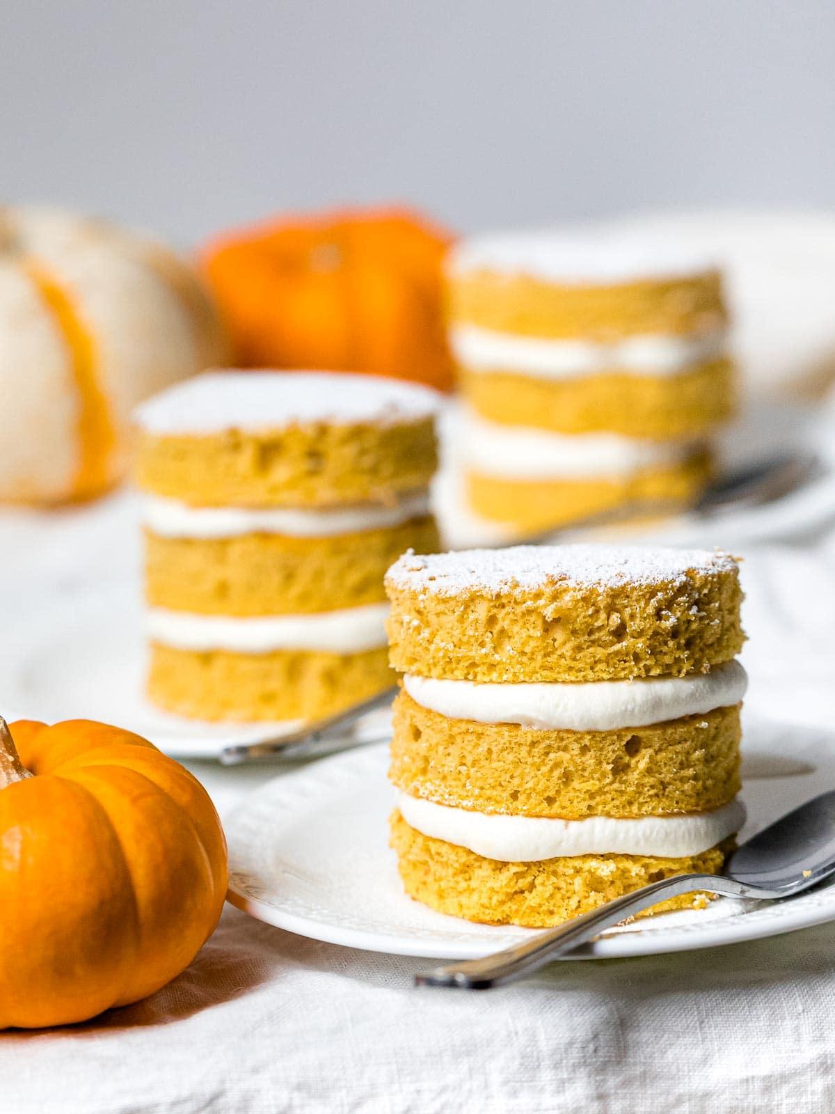 three pumpkin layer cakes on white plates next to mini pumpkins