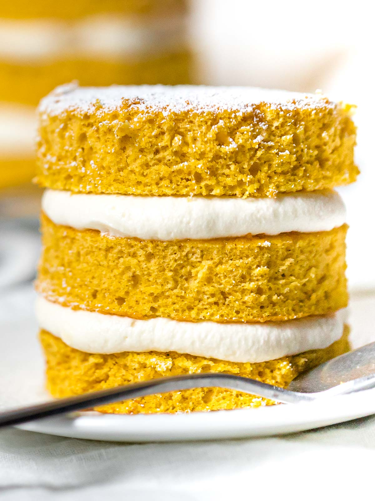 close up of mini pumpkin layer cake with cream cheese frosting on a white plate