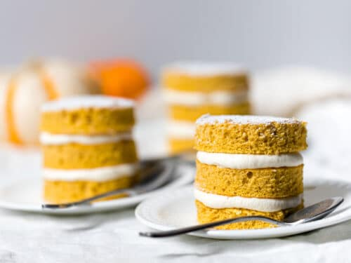 three mini pumpkin cakes with cream cheese frosting on a white plate with a spoon