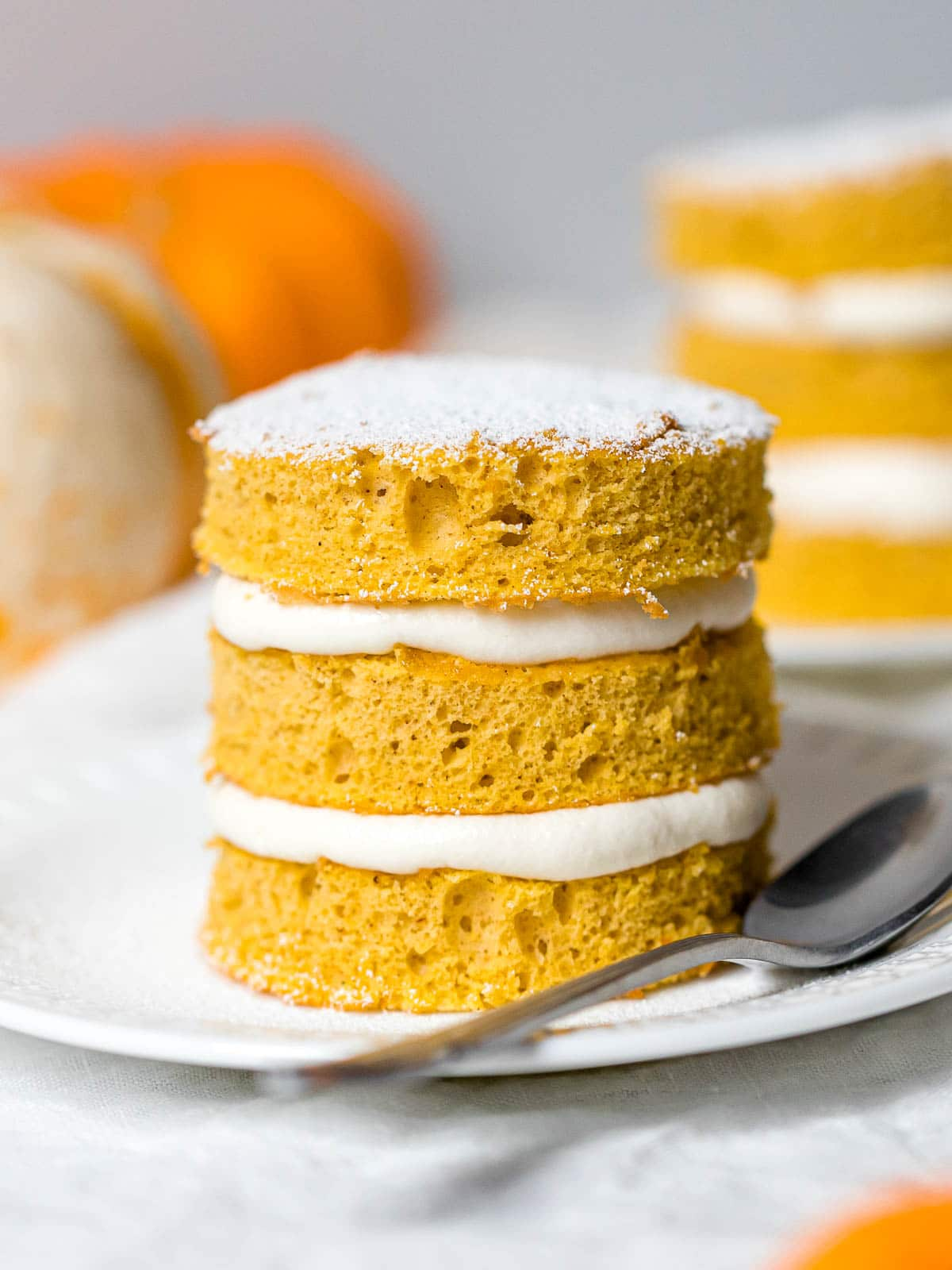 close up of a mini pumpkin cake layered with cream cheese frosting on a white plate with a spoon