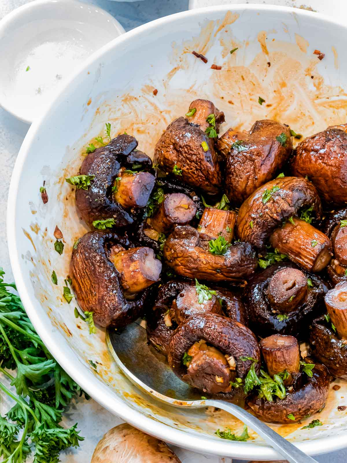 oven roasted mushrooms with garlic and soy sauce sprinkled with parsley in a white bowl with a metal spoon