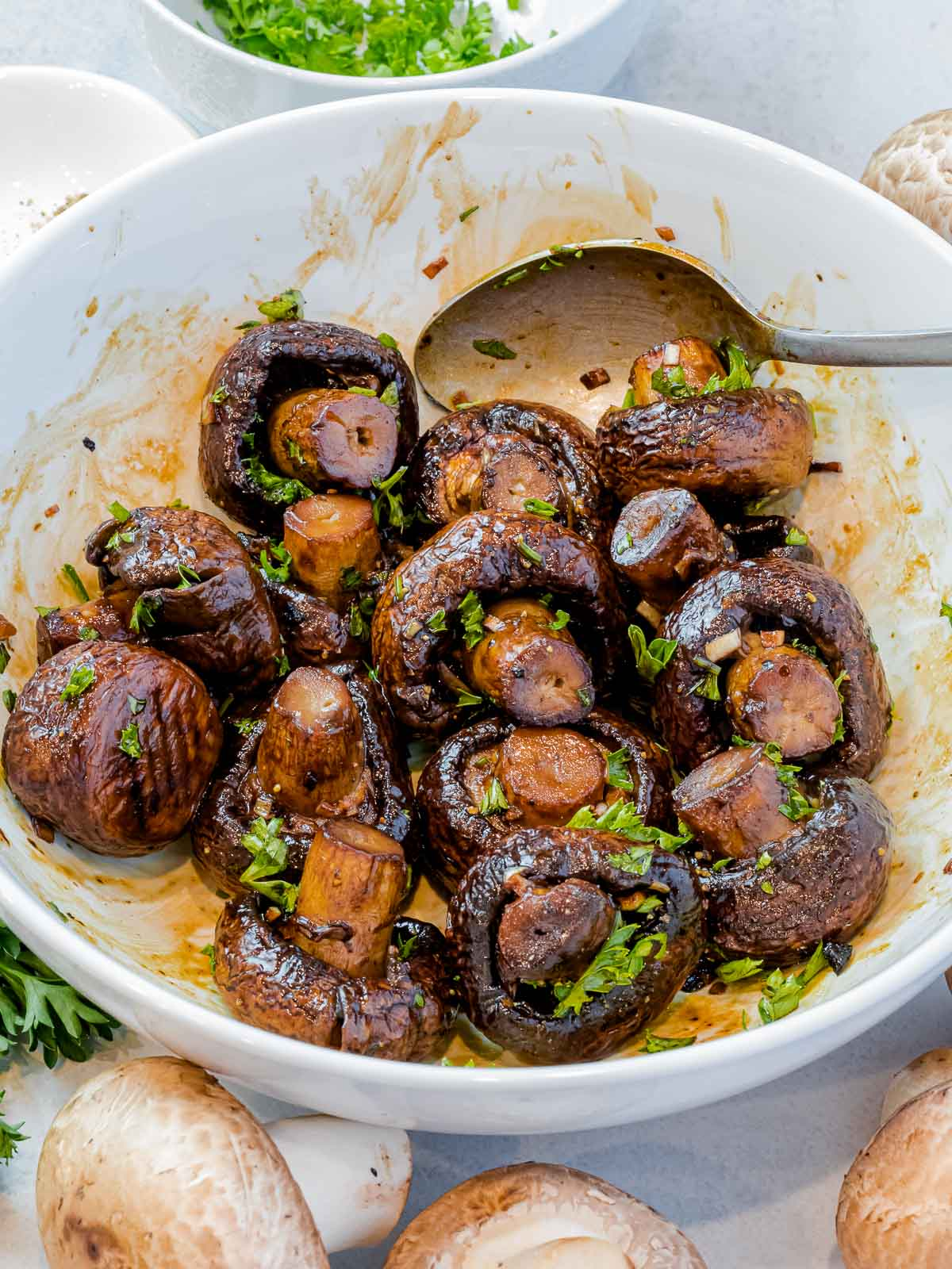 oven roasted mushrooms in a white bowl with a spoon surrounded by raw mushrooms