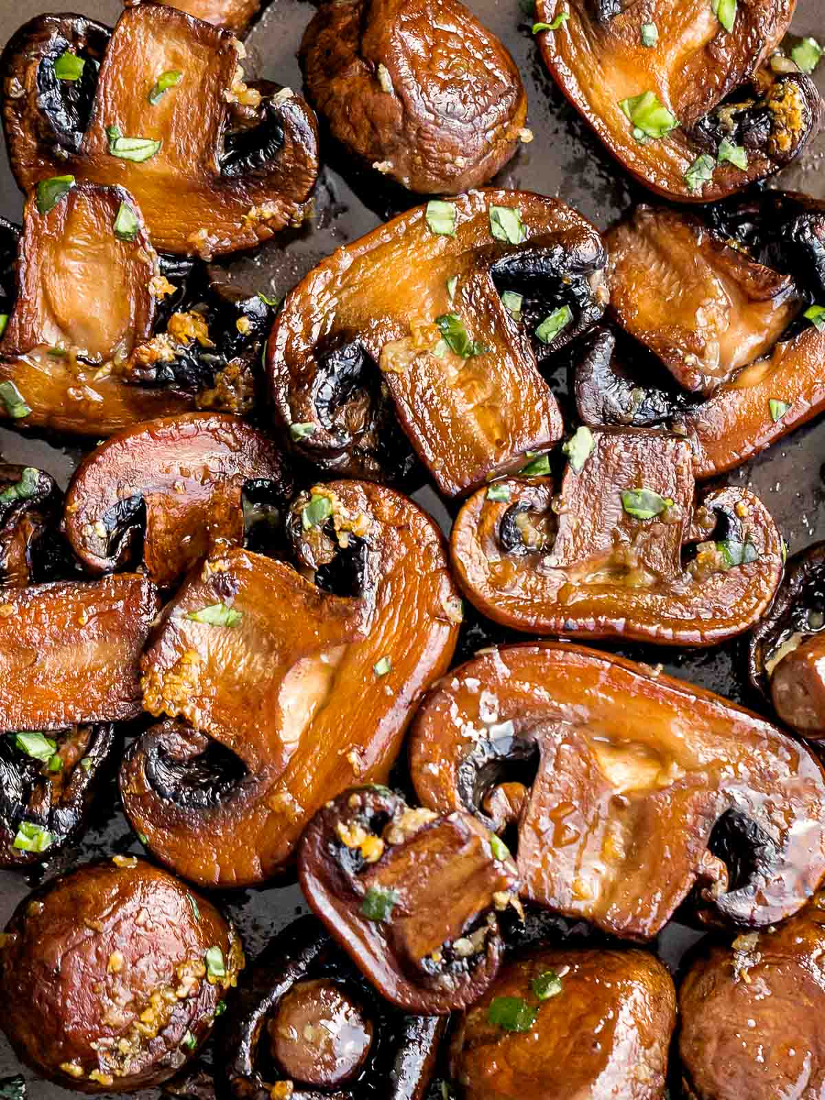 sauteed mushrooms laying flat on a pan and garnished with chopped parsley