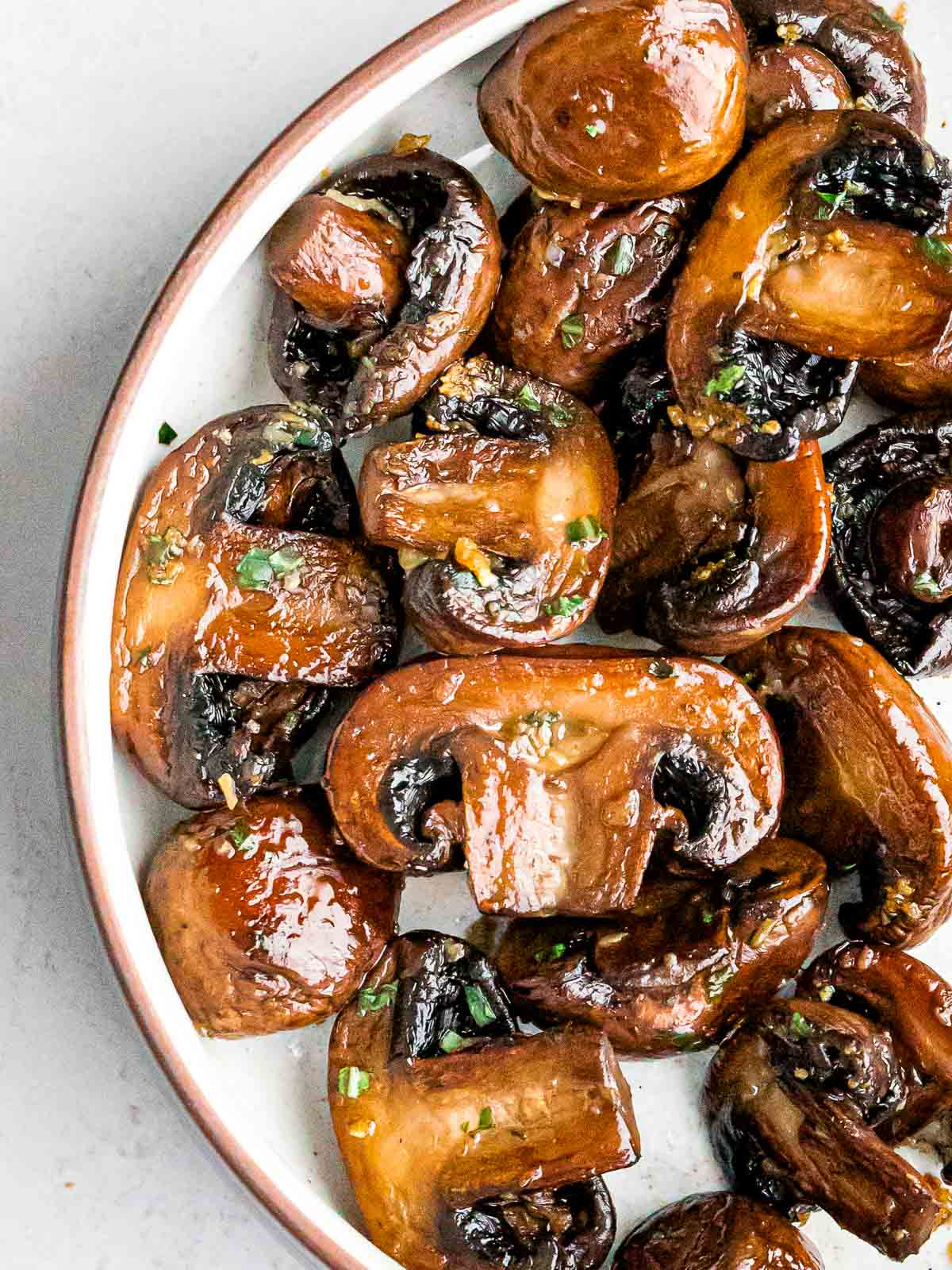 overhead of golden brown sauteed mushrooms with garlic and chopped parsley