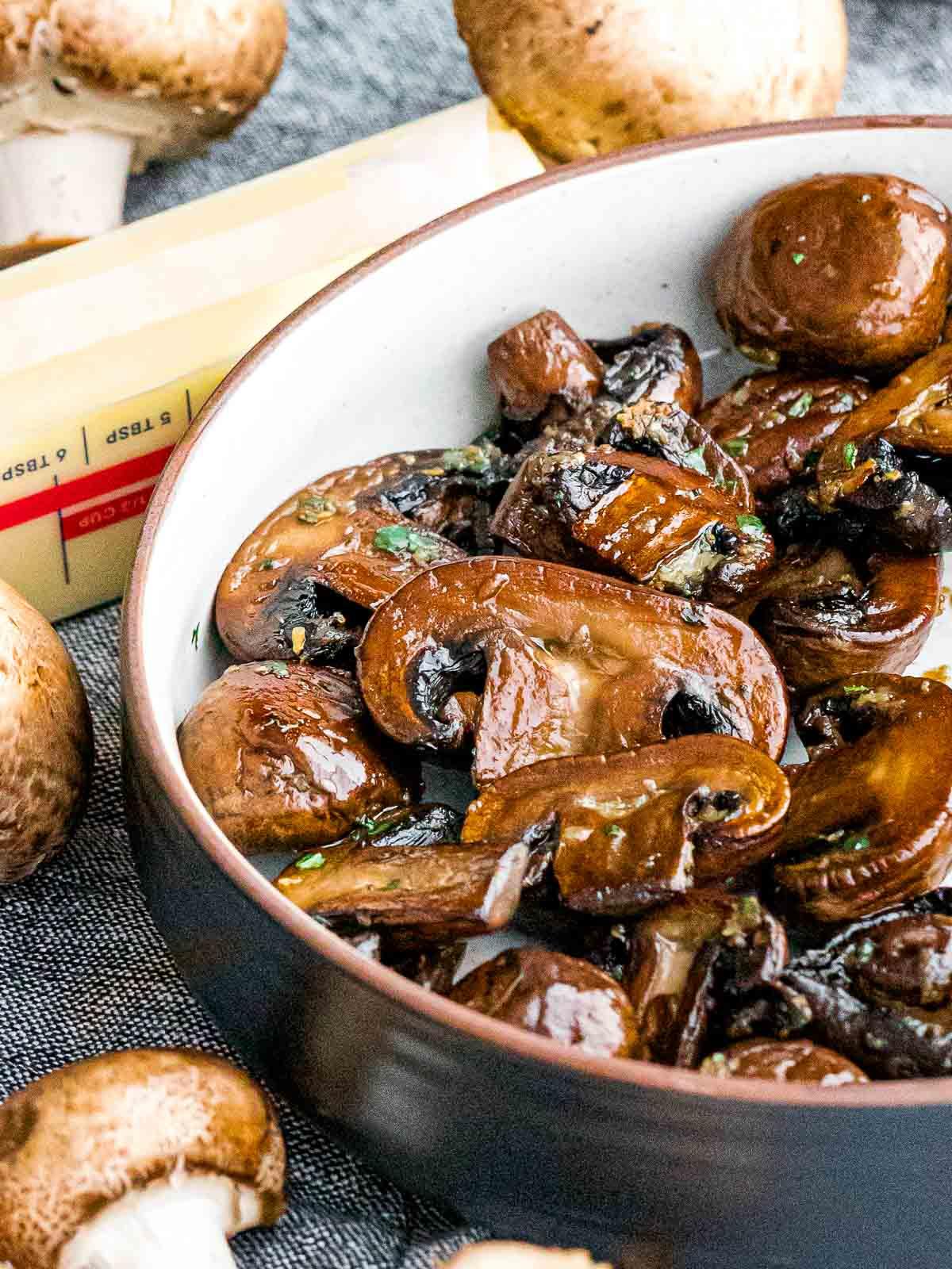 golden brown garlic butter mushrooms in a bowl next to a stick of butter