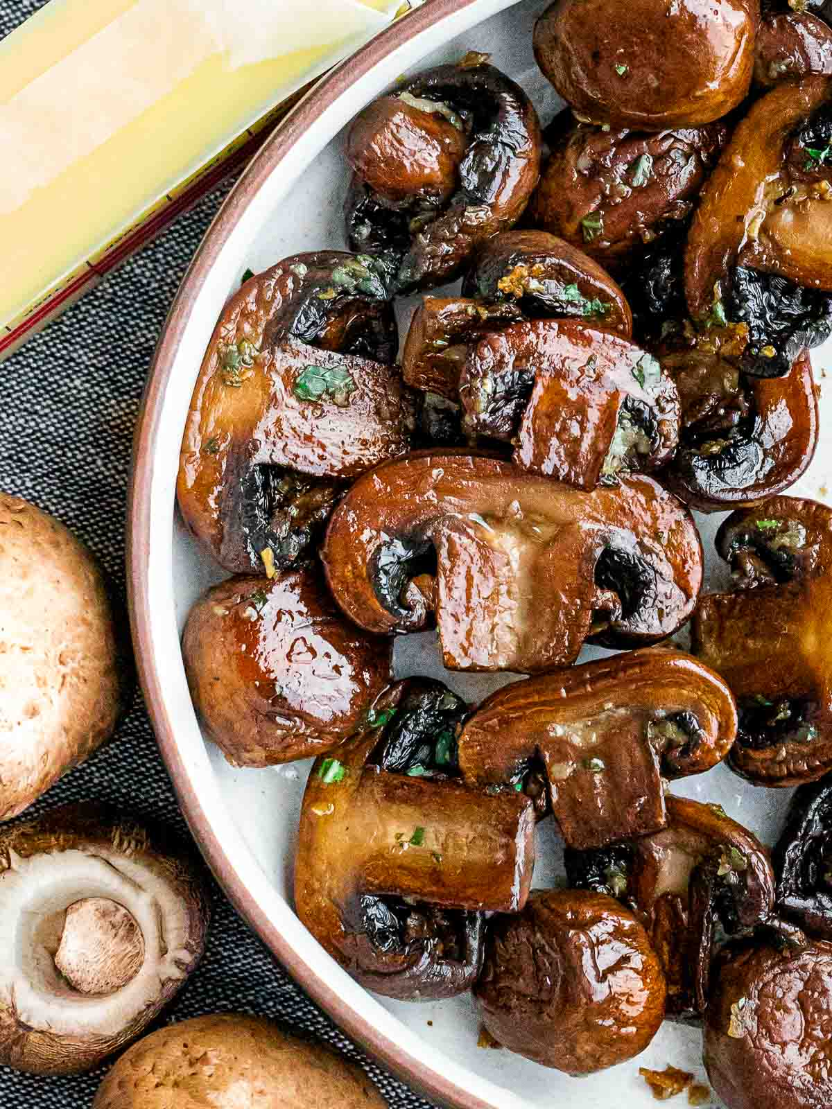 close up of sauteed mushrooms next to butter and uncooked mushrooms