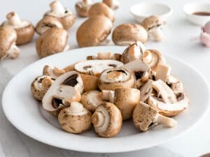 baby portabello mushrooms washed and prepped on a white plate