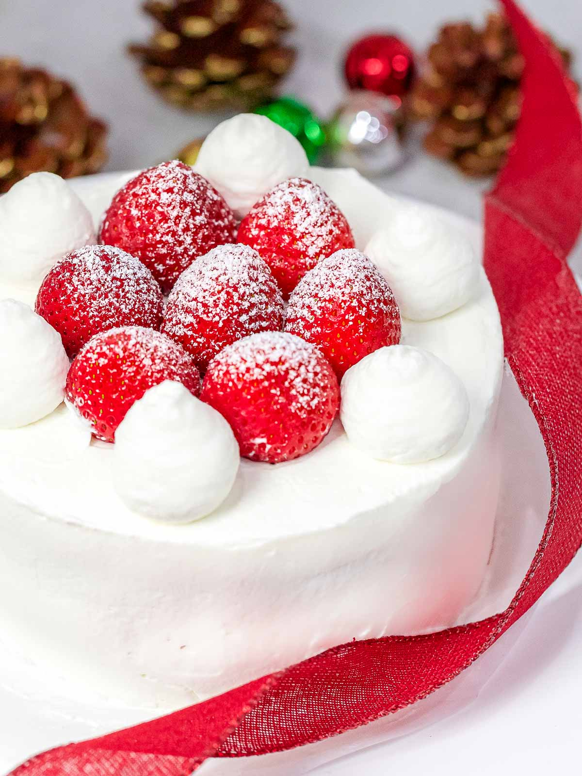 Japanese Christmas cake decorated with fresh strawberries and whipped cream next to red ribbon, Christmas ornaments, and pine cones in the background