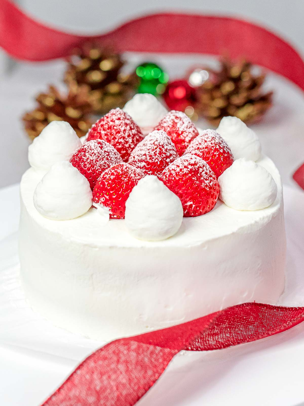 Japanese Christmas cake decorated with whole strawberries dusted with powdered sugar with Christmas ornaments, red ribbon, and pine cones in the back