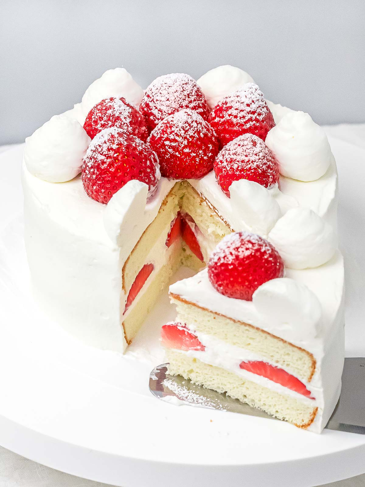 a slice of fresh strawberry cream cake next to whole cake with strawberries and whipped cream