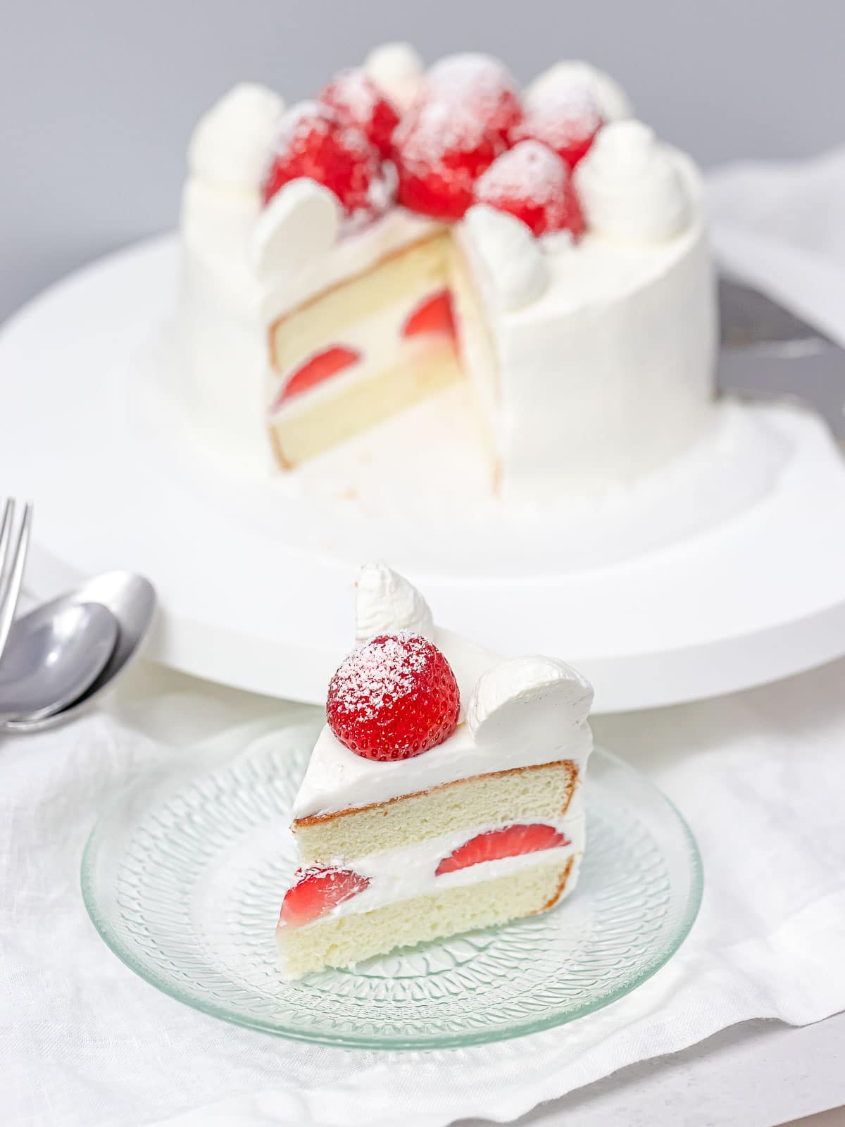 a slice of Japanese strawberry shortcake on a glass plate with the whole cake in the background