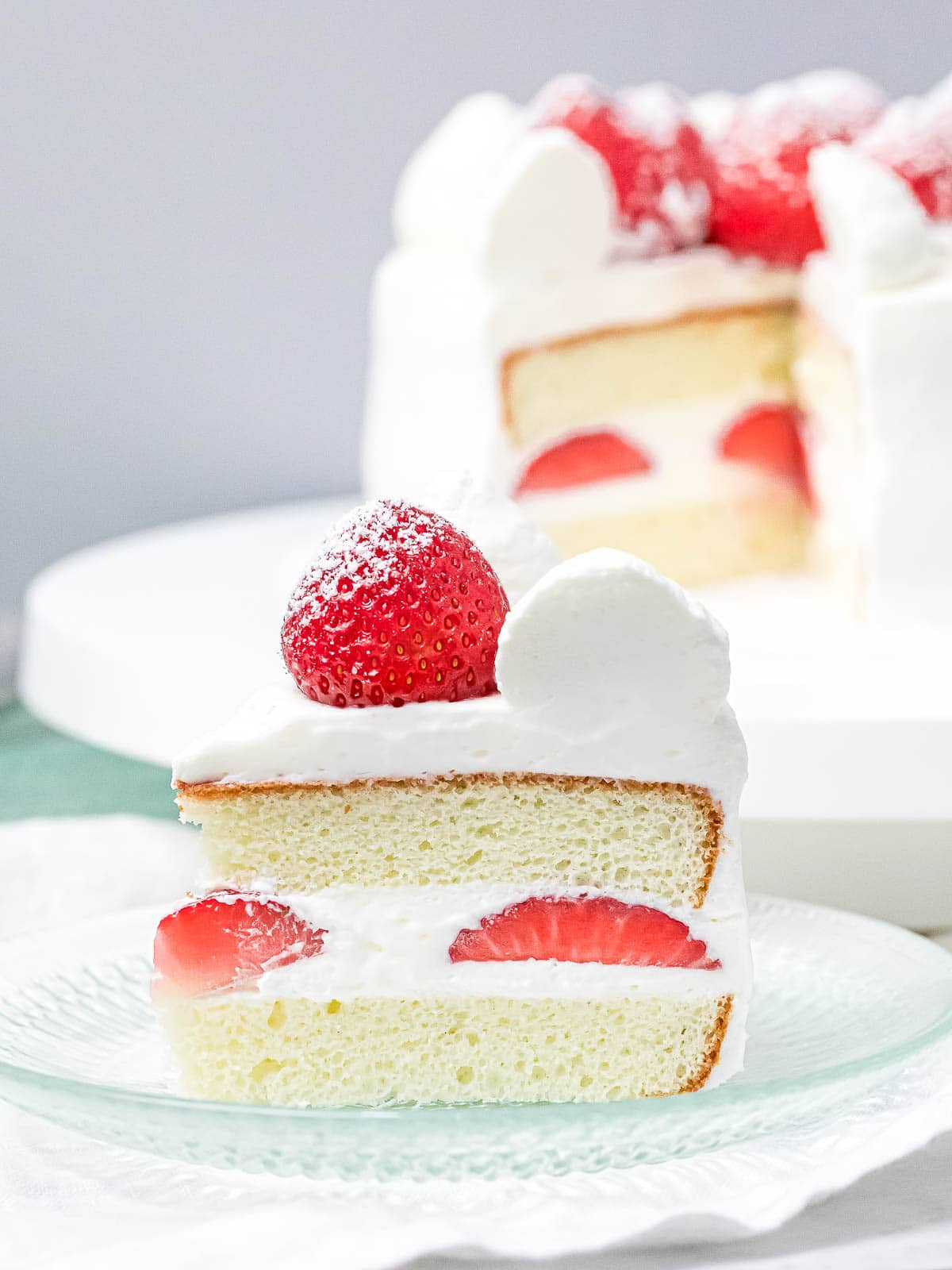 a slice of Japanese strawberry sponge cake on a plate decorated with a whole strawberry and fresh cream