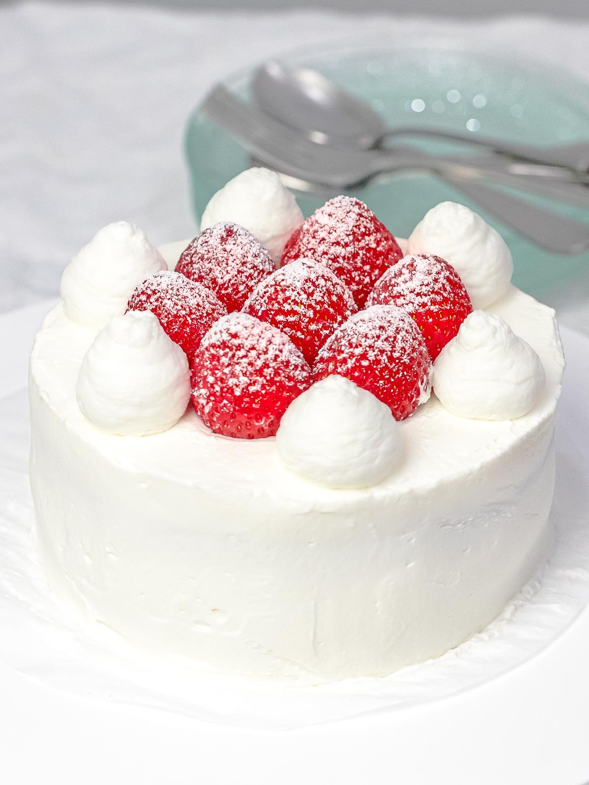 Fresh strawberry cream cake decorated with whole strawberries, powdered sugar, and whipped cream next to plates and utensils