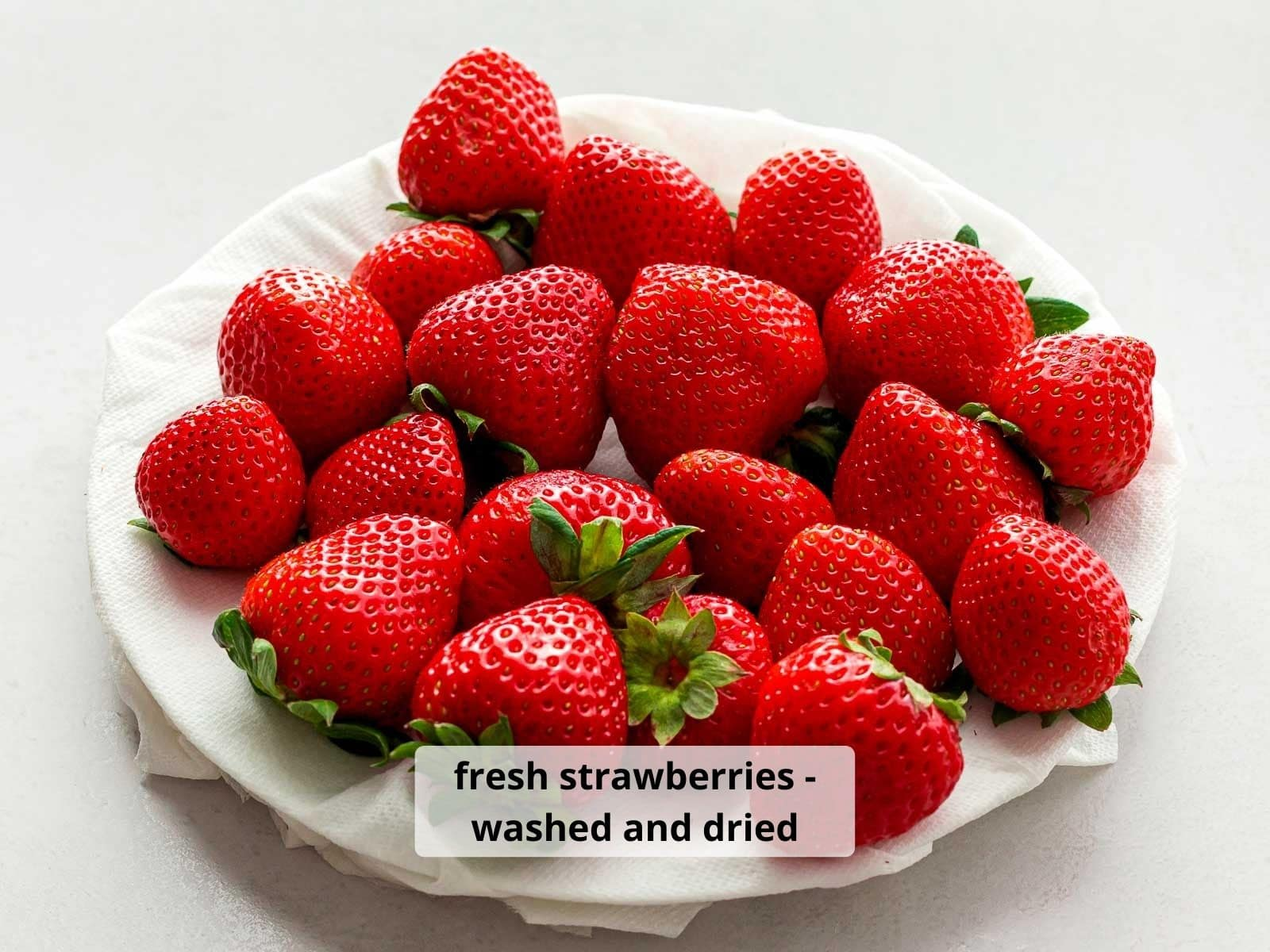 close up of red strawberries washed and dried on a white plate