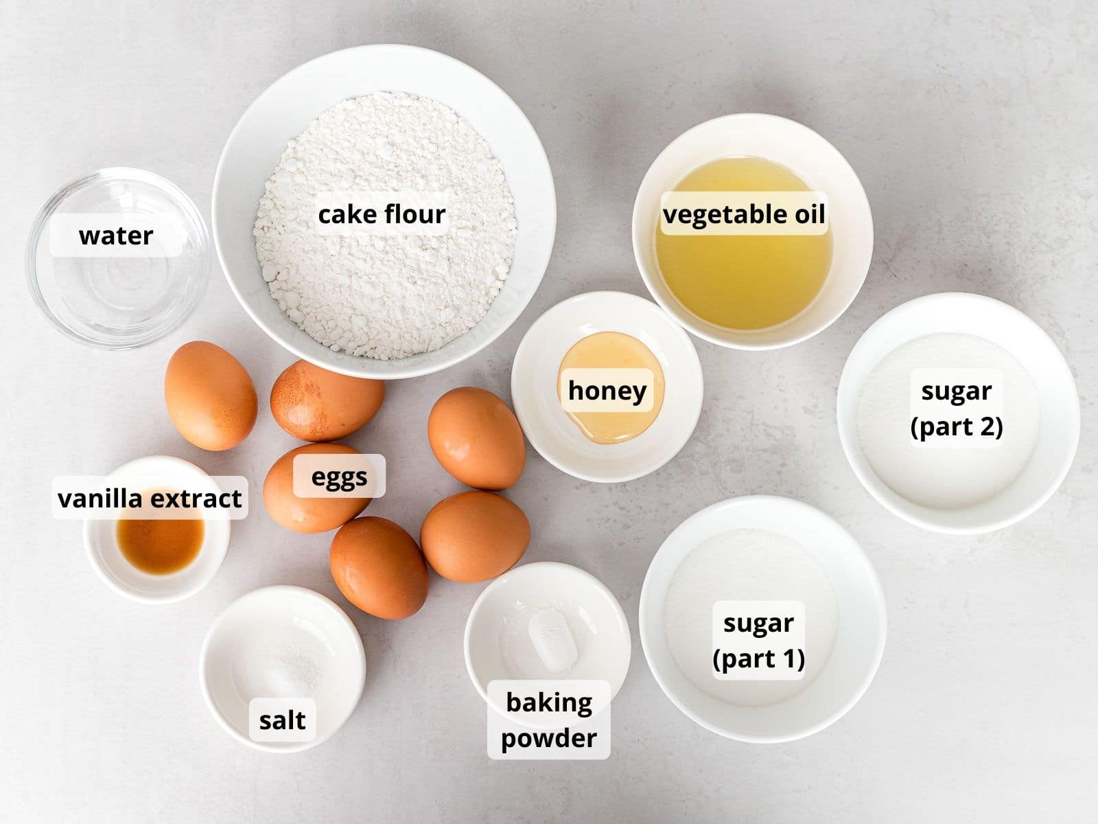 labeled photo of ingredients for Japanese strawberry shortcake in white bowls that includes eggs, cake flour, and sugar
