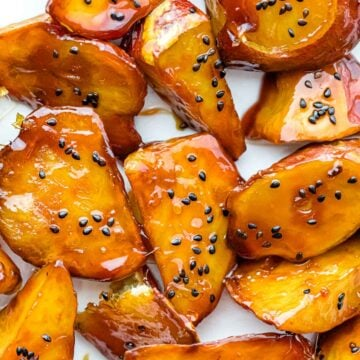Korean candied sweet potatoes with golden caramel coating and black sesame seeds on a white plate