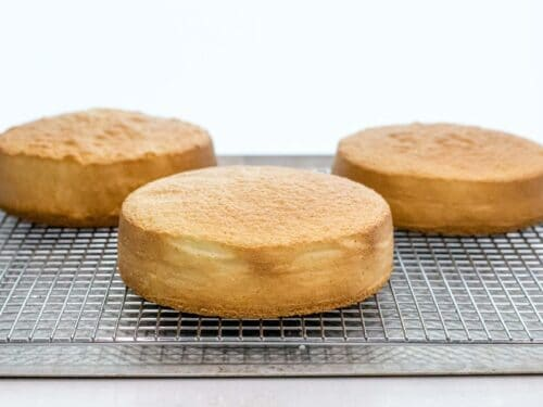 three golden brown and fluffy sponge cakes cooling on a wire rack