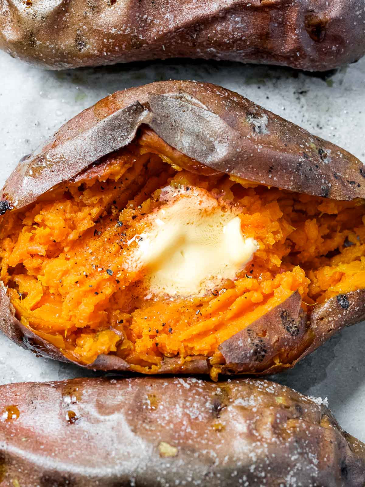 baked potato with crispy skin cut open with a pad of butter in the middle