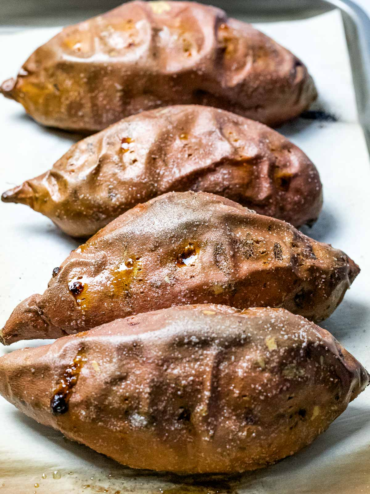 four perfect baked sweet potatoes with crispy, wrinkled skin on a baking pan showing caramelized syrup oozing from the sweet potatoes.