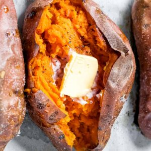 close up of perfect baked sweet potato split open with butter