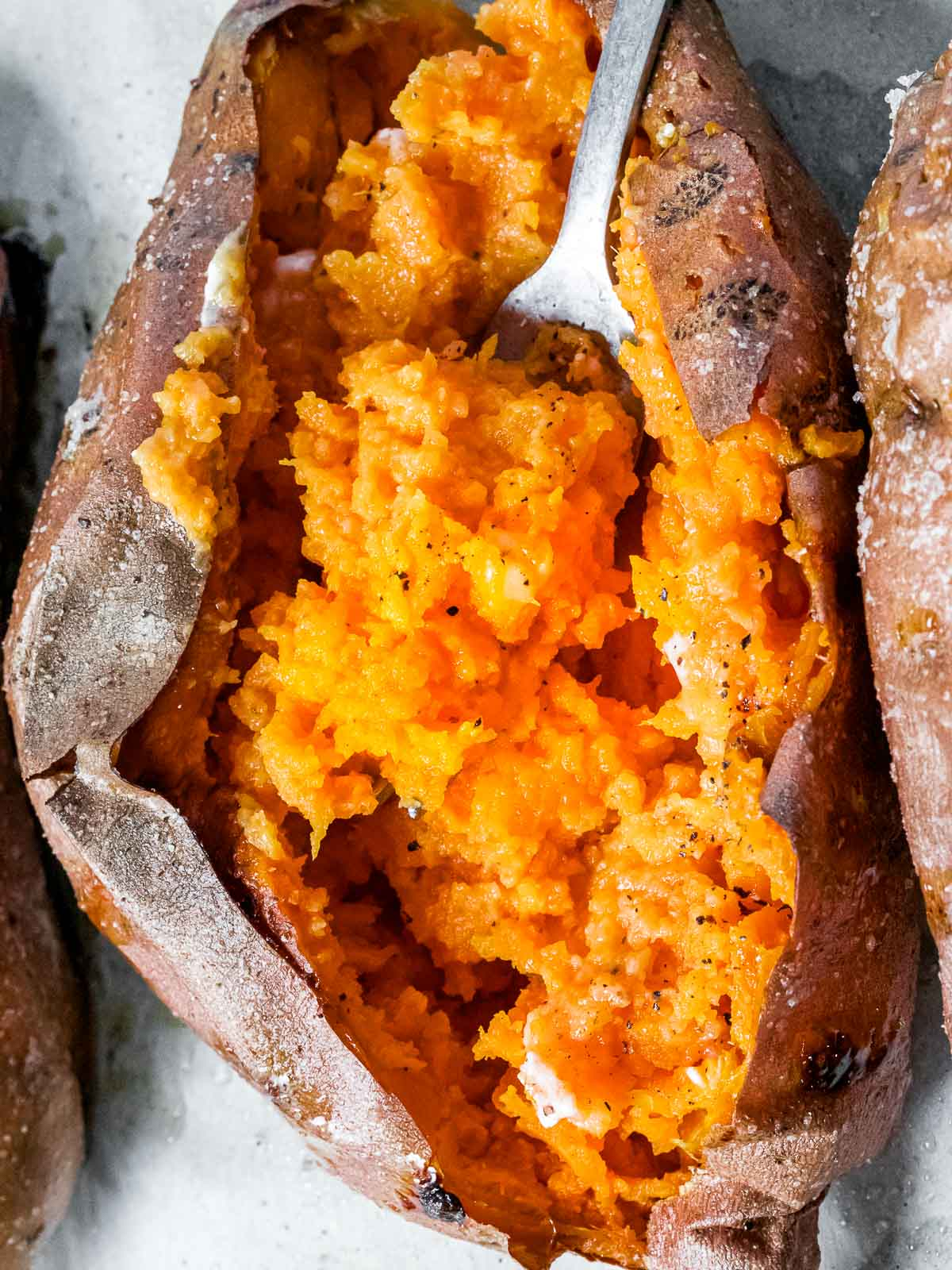 whole roasted sweet potato mashed with a fork