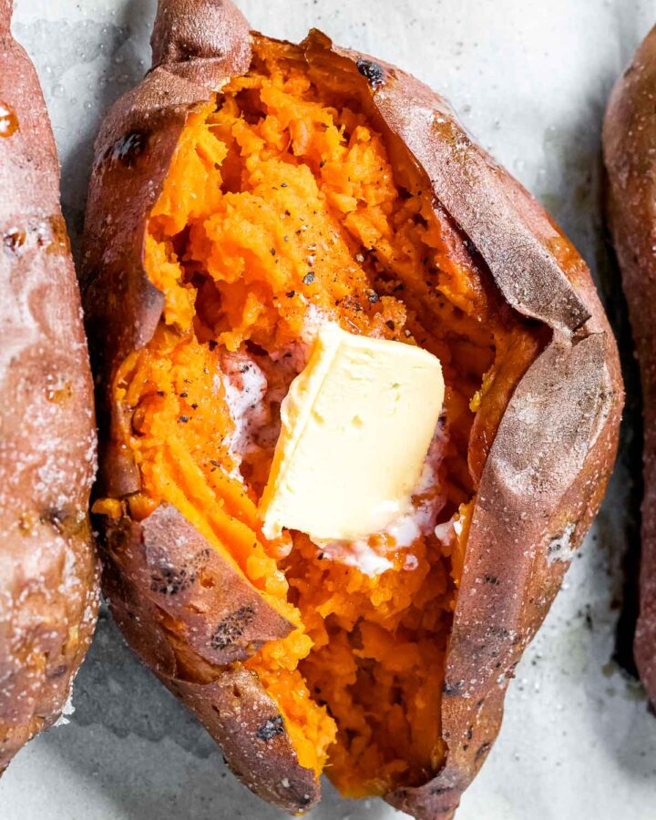 perfect baked sweet potato cut open to reveal soft flesh with a pad of butter on top