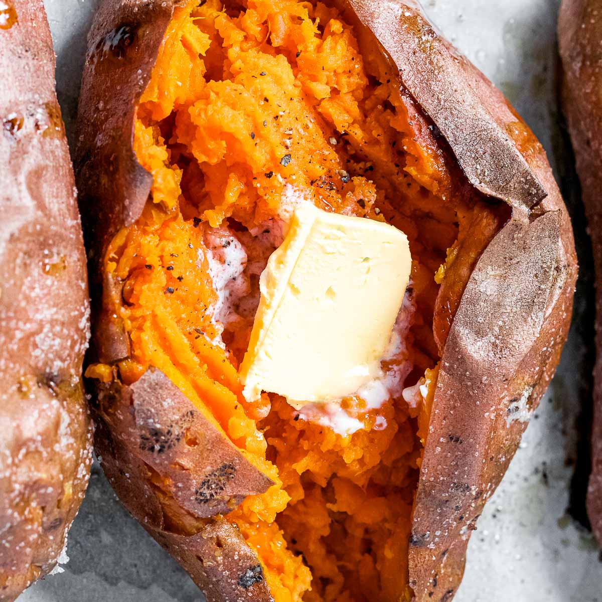 perfect baked sweet potato cut open to reveal fluffy inside with a pad of butter