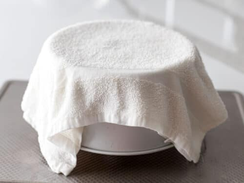 chiffon cake pan turned upside down and covered with a damp towel to cool it down