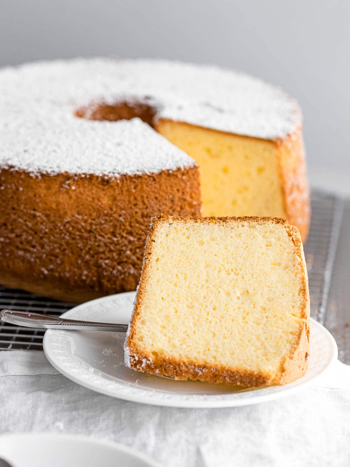slice of fluffy Japanese chiffon cake on a white plate with powdered sugar