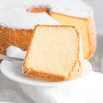a slice of fluffy chiffon cake on a white plate dusted with powdered sugar