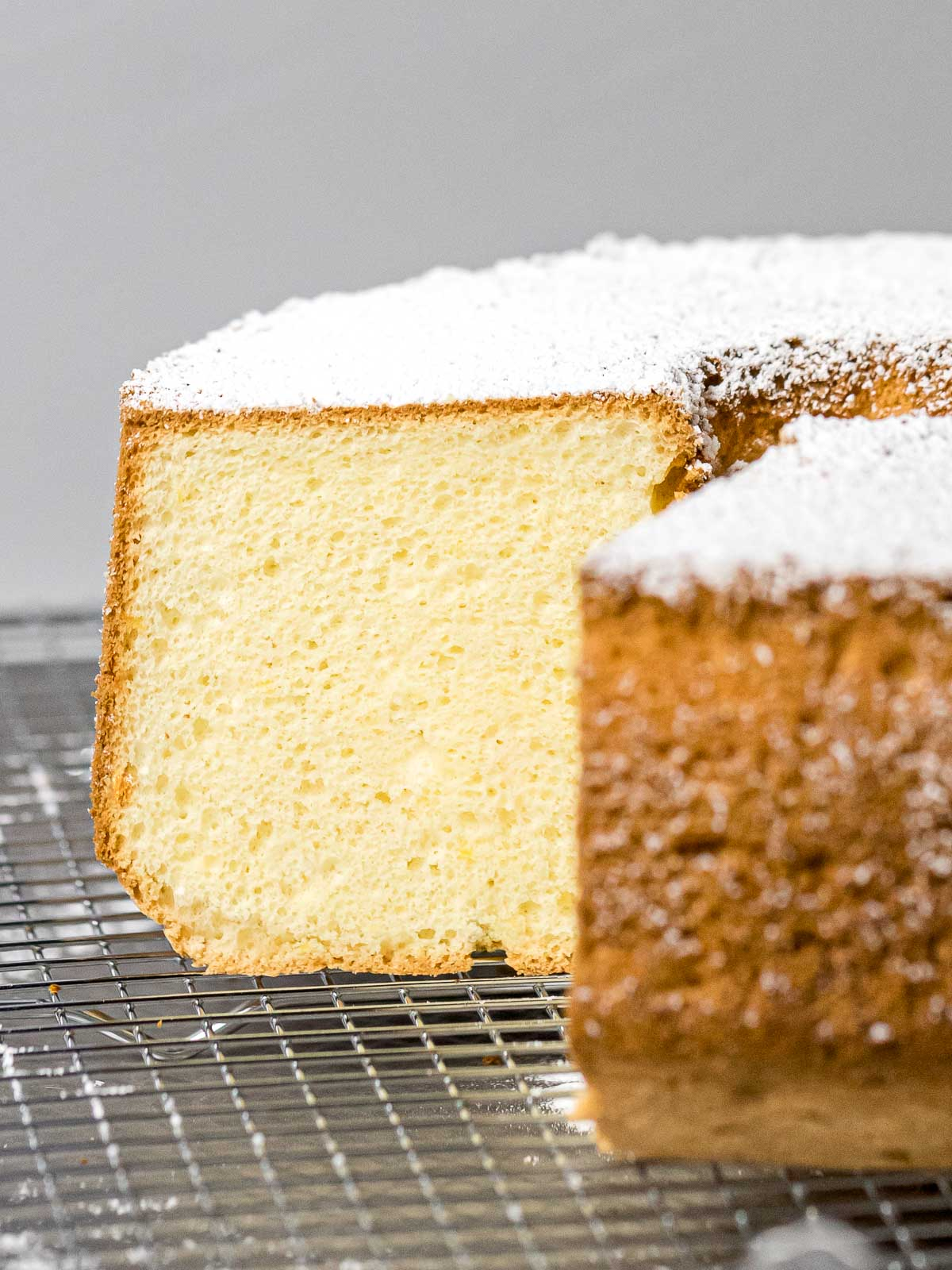 cross section of fluffy chiffon cake on a wire rack dusted with powdered sugar