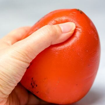 hachiya persimmon being squeezed by a hand to show ripeness
