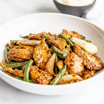 chicken and green bean stir fry in a white bowl