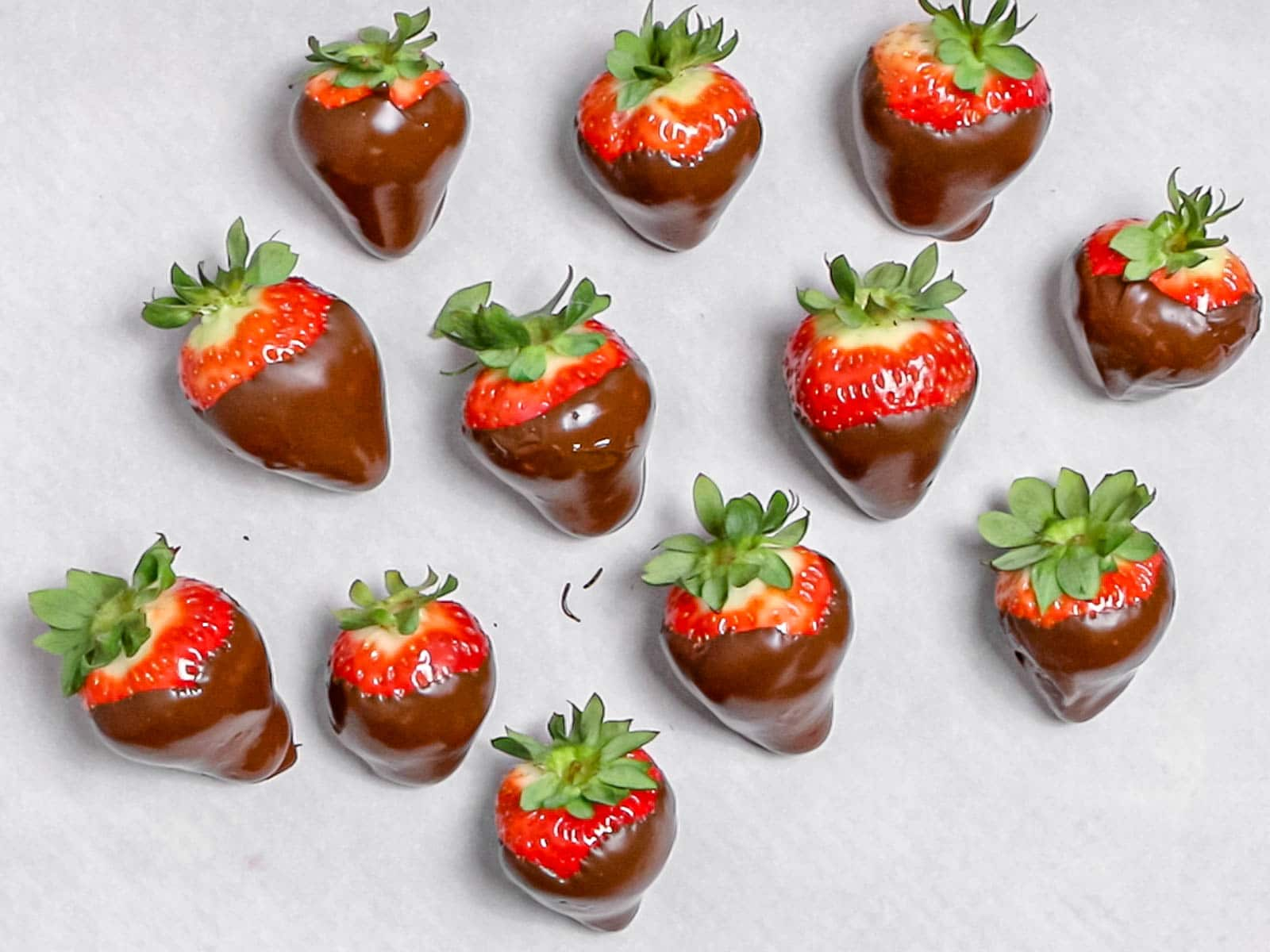 chocolate covered strawberries laying on parchment paper to harden