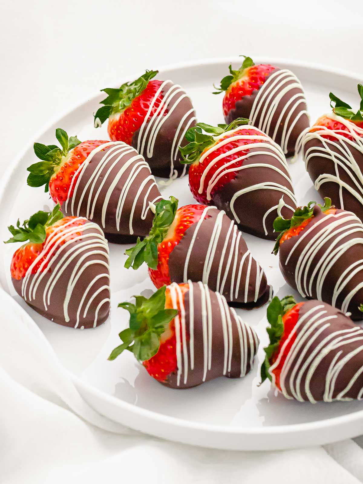 chocolate covered strawberries decorated with white chocolate drizzle on a white plate