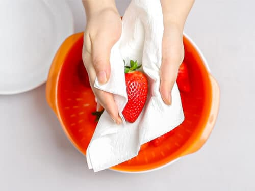 a strawberry being dried with a paper towel over an orange colander