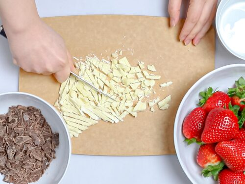 white chocolate being chopped by a knife on a cutting board next to chopped dark chocolate and strawberries in white bowls
