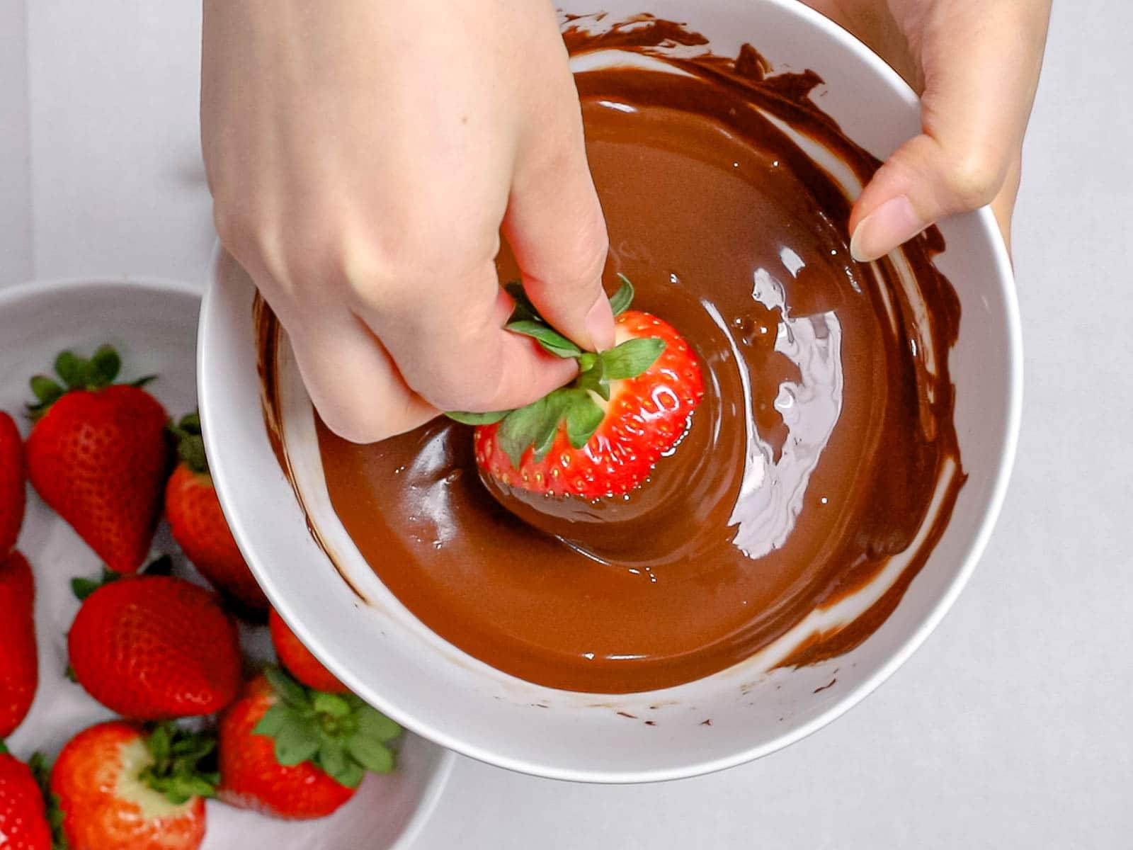 hand dipping a strawberry in melted chocolate
