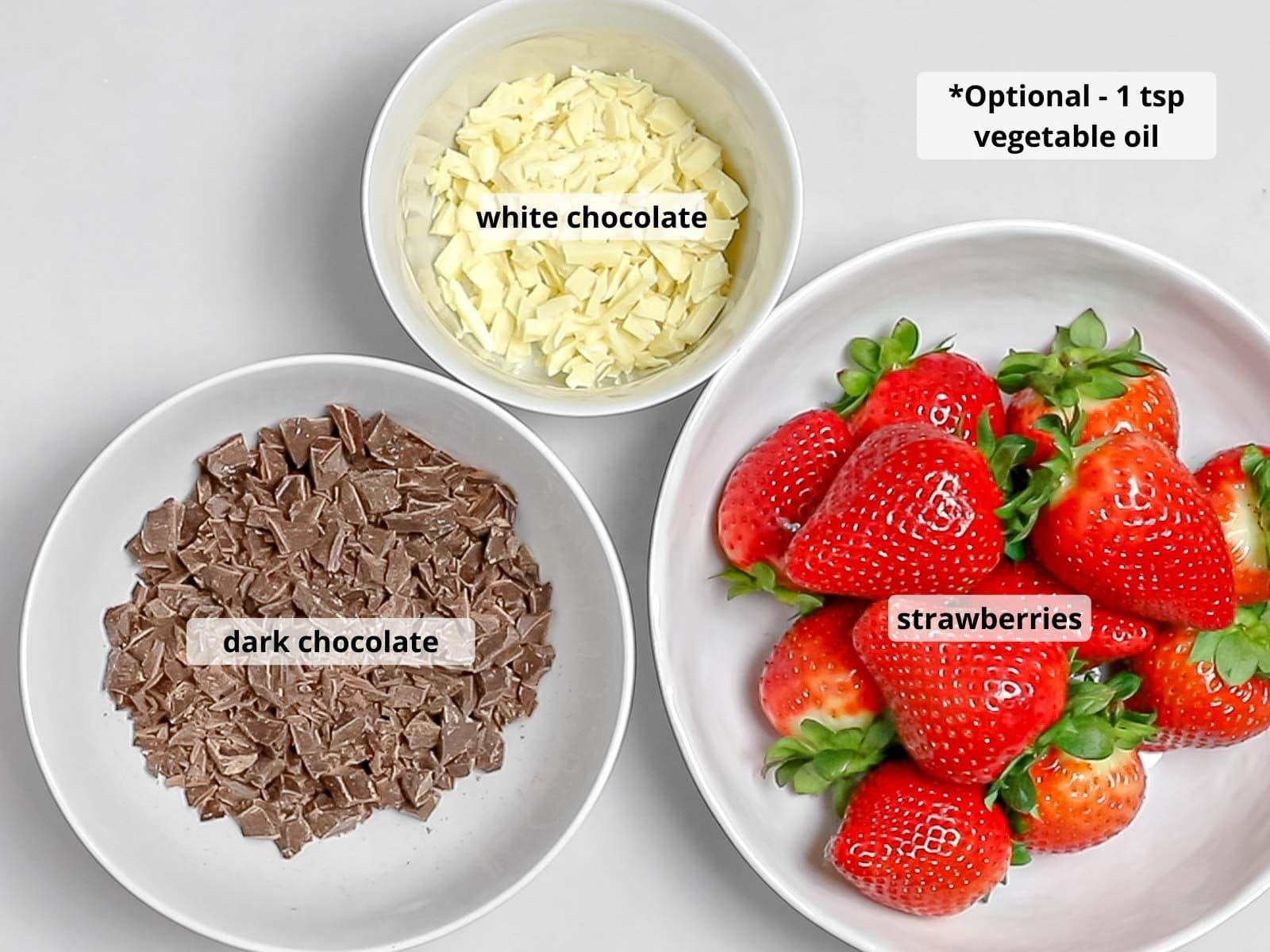 labeled ingredients for chocolate dipped strawberries in white bowls including dark chocolate and white chocolate